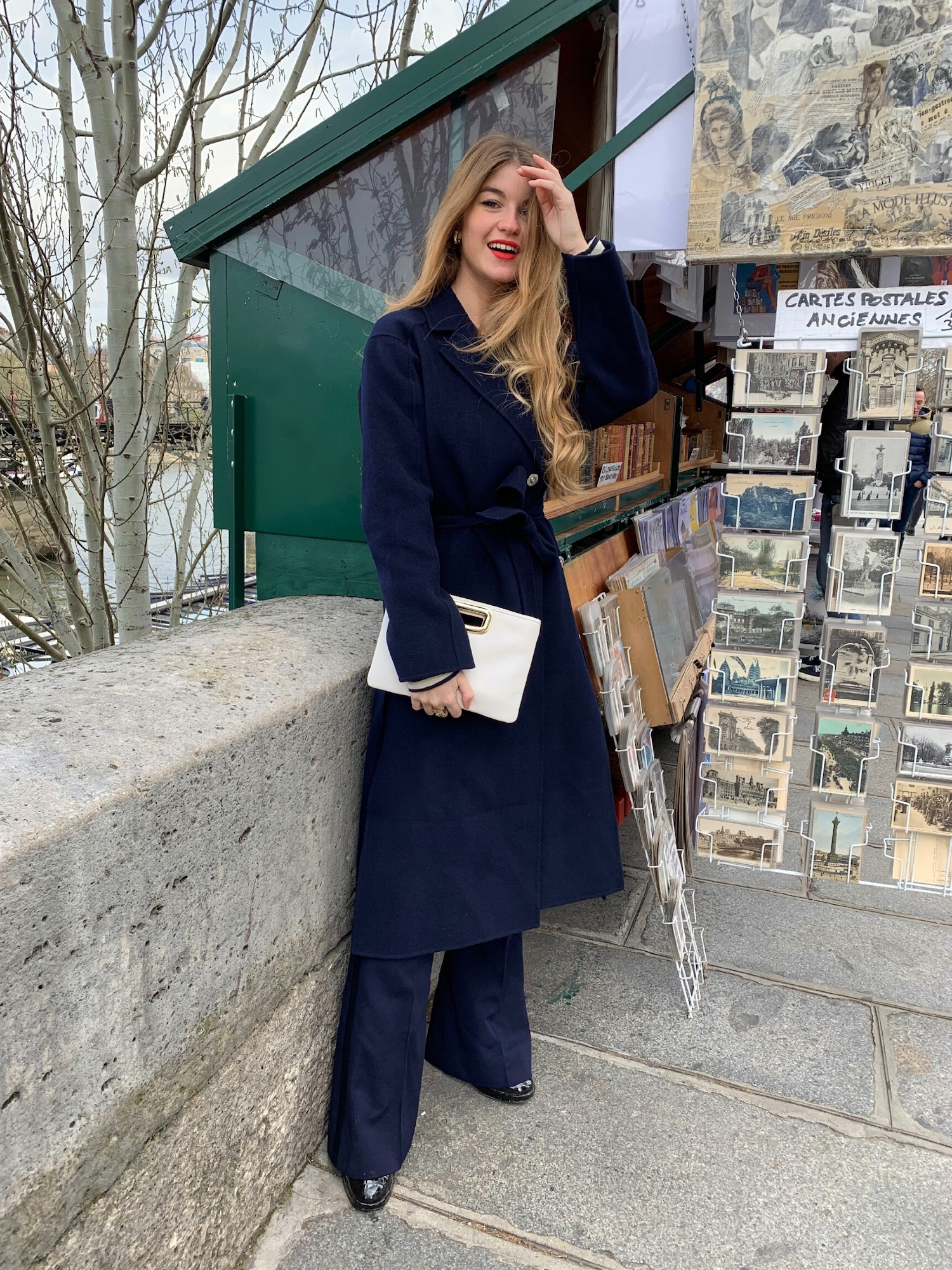 Constance Arnoult wearing a navy wool coat near the bouquinistes of Paris